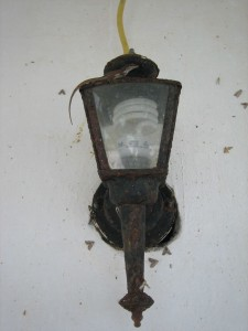 Old balcony lamp with a lizard requesting we upgrade to a standard more fitting to a grand museum.
