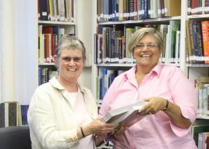 Ann Pienkowski (UKOTCF) gifting books to Director of the TCNM, Pat Saxton